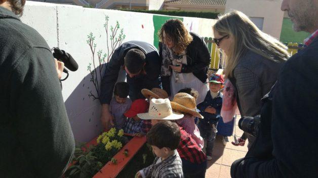 Los concejales Antonio Luego y Estíbaliz Masegosa ayudan a los peques a plantar las primeras lechugas.